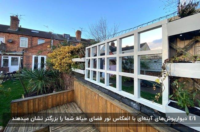 دیوارپوش آینه ای مشبک با فریم سفید در حیاطی با دیوارپوش چوبی نیمه دیوار