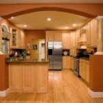 آشپزخانه ای با کابینت های چوبی قهوه ای ، سقف هالوژن دار گلبهی و دیوار و آرگ آجری رنگ گچی
