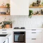 آشپزخانه ای با کابینت های سفید، کاشی های بین کابینتی سفید و قفسه های دیواری چوبی با گلدان های گل