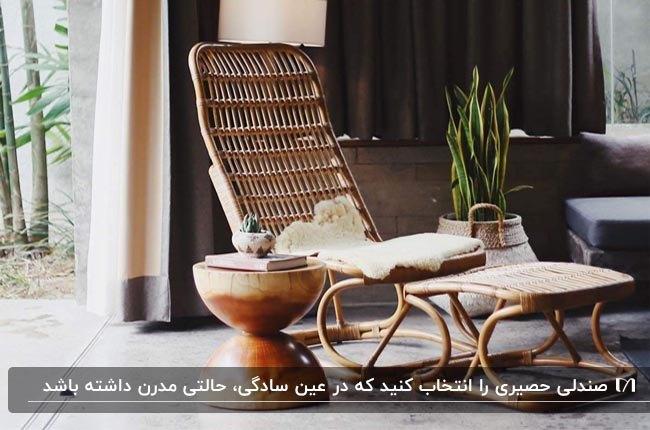 صندلی راحتی حصیری و پاف زیر پا کنار یک میز گرد چوبی و گلدان گل سانسوریا