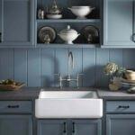 آشپزخانه ای با کابینت های آبی و دستگیره های مشکی به همراه سینک تک لگنه سفید
