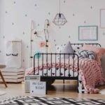 دکوراسیون اتاق خواب دخترانه ای با تخت مشکی، فرش طرح دار سفید و مشکی و کاغذدیواری طرحدار