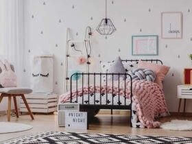 دکوراسیون اتاق خواب دخترانه ای با تخت فلزی مشکی، فرش طرح دار سفید و مشکی، روتختی صورتی و کاغذدیواری سفید با طرح مشکی