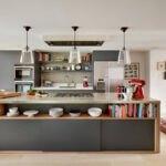 آشپزخانه ای با کابینت ها و جزیره خاکستری به همراه قفسه چوبی پشت جزیره برای کتاب و دکوری ها