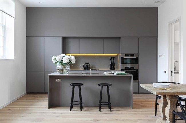 آشپزخانه کوچک و مدرنی با کابینت ها و جزیره خاکستری با چهارپایه مشکی