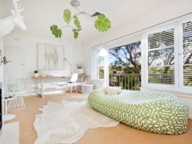 تصویر یک اتاق خانه بدون مبل با تشک دراز سفید و سبز مقابل شومینه و فرش خزدار سفید
