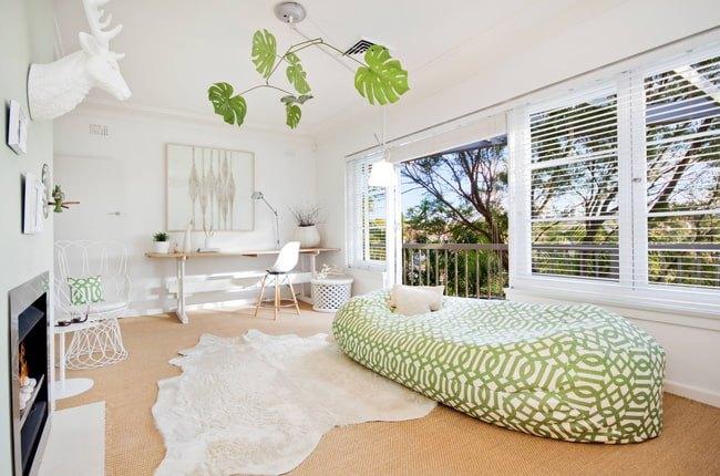 تصویر یکی از اتاق های خانه بدون مبل با تشک دراز سفید و سبز مقابل شومینه و فرش خزدار سفید