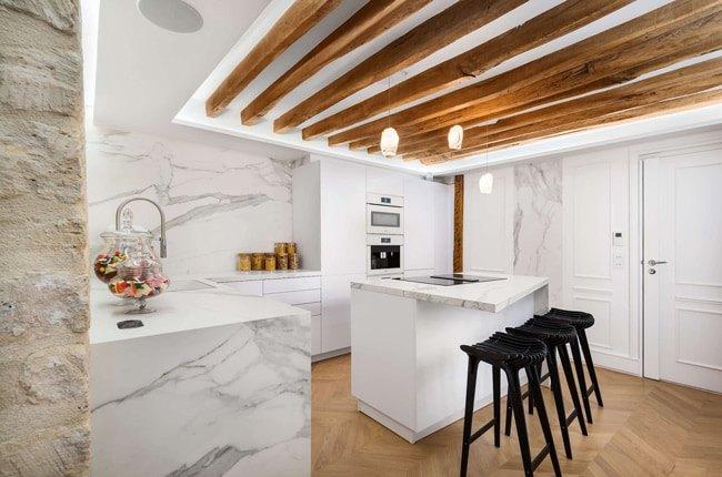 آشپزخانه سفیدی با تیرهای چوبی در سقف و سنگ روی کابینت و اپن مرمر سفید