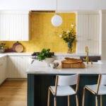 آشپزخانه ای با کابینت های سفید، کانتر سبز تیره با صفحه رویی سفید با کاشی های بین کابینتی زرد رنگ