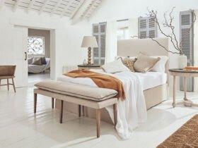 اتاق مستر سفید رنگی با تخت دو نفره و پاف کرم رنگ، روتختی سفید، کرم و خردلی با آباژور و گلدان و شاخه اطراف تخت