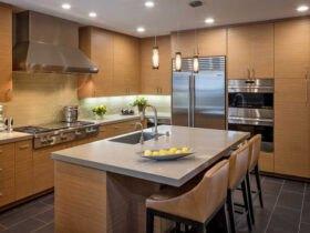 آشپزخانه بزرگی با کابینت ها و جزیره به رنگ چوب به همراه نورپردازی های نقطه ای