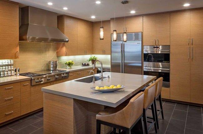آشپزخانه بزرگی با کابینت ها و جزیره به رنگ چوب با صفحه روییی کابینت طوسی به همراه نورپردازی های نقطه ای