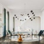 نشیمنی با پرده های سبز و سفید، کاناپه طوسی روشن و دو صندلی سبز به همراه لوستر مدرن مشکی