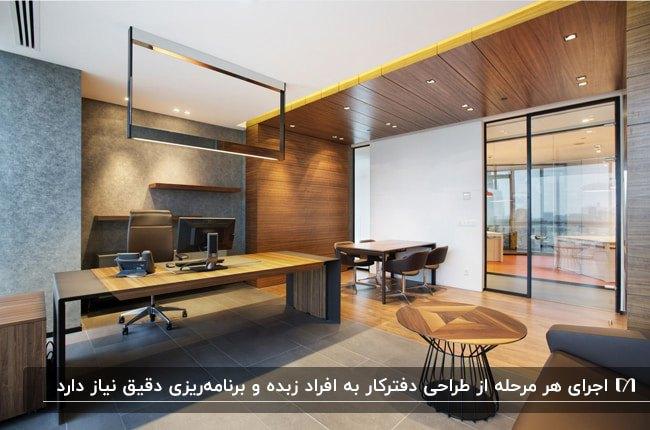 طراحی دفتر کاری با ترکیب چوب و رنگ طوسی زغالی، میز عسلی گرد چوبی با پایه فلزی مشکی و میز کار چوبی