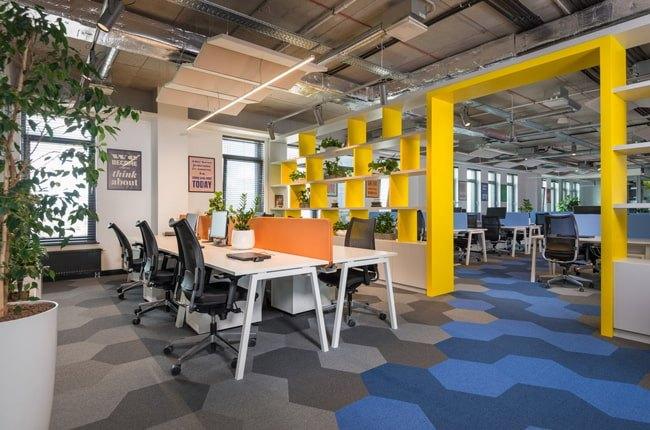 طراحی دفتر کار با کفپوش لانه زنبوری طوسی و آبی، قفسه های زرد، میزو صندلیهای سفید و مشکی