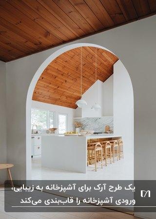 آشپزخانه ای مینیمال با سقف شیبدار چوبی، کابینت ها و جزیره سفید، چهارپایه های چوبی و آرک دایره ای گچی