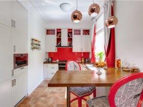 آشپزخانه کمجا با کابینت سفید، بین کابینتی قرمز و کانتر تاشو چوبی