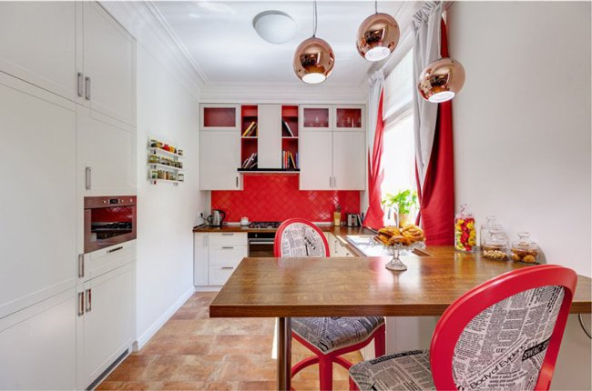 آشپزخانه ای کم جا با کابینت های سفید، دیوار بین کابینت قرمز ، کانتر تاشوی چوبی و صندلی های سفید و قرمز
