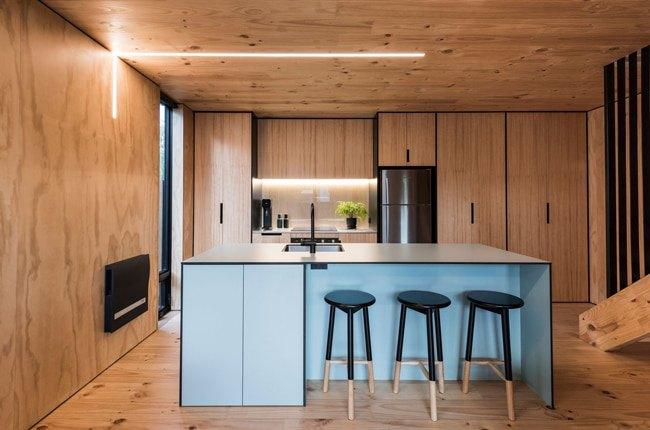 آشپزخانه ای با کابینت ها، سقف، دیوار و کف چوبی به همراه جزیره آبی و سه چهارپایه مشکی