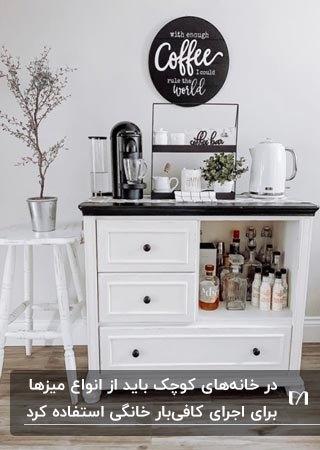 کافی بار خانگی سفید رنگ با صفحه قهوه ای تیره، ماگ و لیوان و فنجان و قهوه ساز و فلاکس روی آن