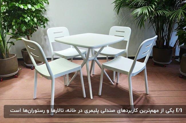 میز و صندلی های سفید رنگ پلیمری برای فضای پاسیو با گلدان های گل