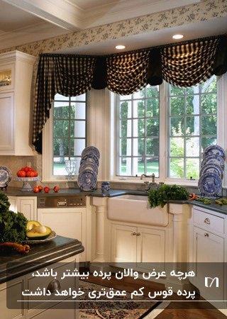 آشپزخانه ای با کابینت های سفید و پرده آشپزخانه قهوه ای با والان قوس دار