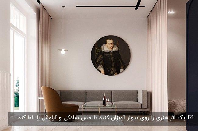 دکوراسیون مینیمال نشیمنی با مبل طوسی و قهوه ای و تابلوی هنری گرد روی دیوار