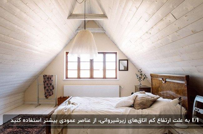 دکوراسیون اتاق زیرشیروانی با تیرهای رنگ شده سقف، تخت دو نفره چوبی و لوستر آویز سفید
