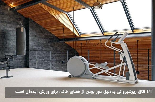 دکوراسیون اتاق ورزش زیرشیروانی با دیوارپوش چوبی قهوه و سنگی زغالی و لوازم ورزشی