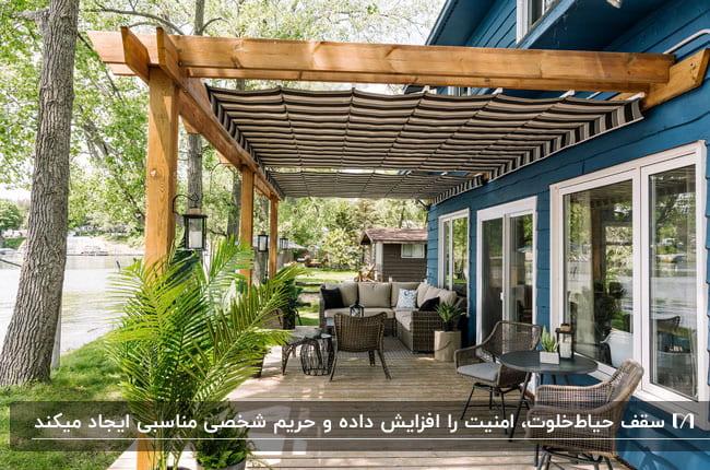 سقف حیاط خلوت با فریم چوبی برای خانه ای ویلایی با نمای آبی با مبلمان و صندلی های حصیری