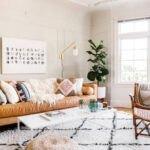نشیمنی به سبک بوهو با مبل چرم قهوه ای، صندلی حصیری و فرش طرحدار کرم و مشکی