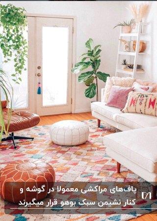 نشیمنی به سبک بوهو با مبل ال سفید، فرش رنگی و دو پاف مراکشی سفید و قهوه ای