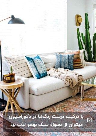 نشیمنی به سبک بوهو با مبل سفید و کوسن های آبی و میز عسلی چوبی