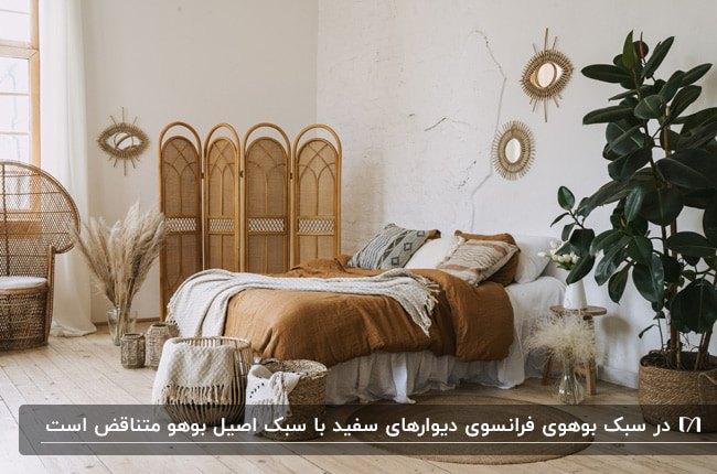 اتاق خوابی به سبک بوهو با تخت دونفره، پارتیشن حصیری و گلدان گل فیکوس