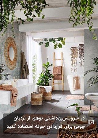 سرویس بهداشتی به سبک بوهو با گلدان های گل، وان و نردبان چوبی برای حوله