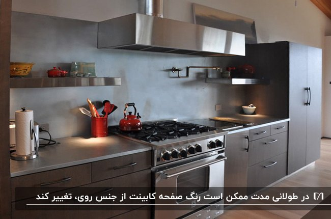 آشپزخانه ای با کابینت های خاکستری و صفحه کابینت از جنس فلز روی