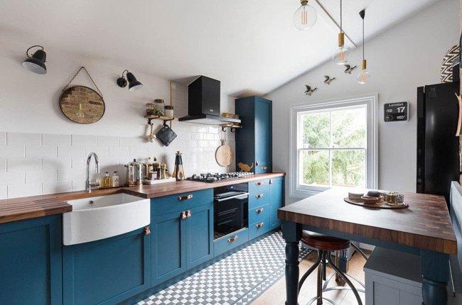 آشپزخانه ای زیرشیروانی با کاشی های سفید، کابینت آبی و صفحه کابینت چوبی رگه دار قهوه ای