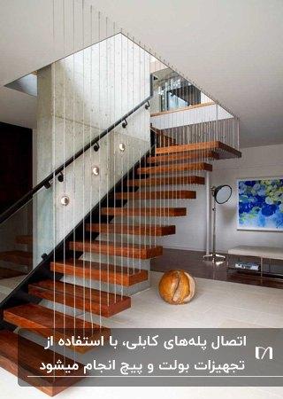 پله معلق کابلی با پله چوبی و حفاظ کابلی، تابلوی نقاشی و آباژور پایه بلند