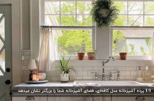آشپزخانه ای با کابینت ها و کاشی بین کابینتی سفید به همراه پرده آشپزخانه مدل کافه ای
