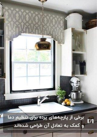 آشپزخانه ای با کابینت های کرم و قهوه ای و پرده آشپزخانه طرح دار کرم و سفید