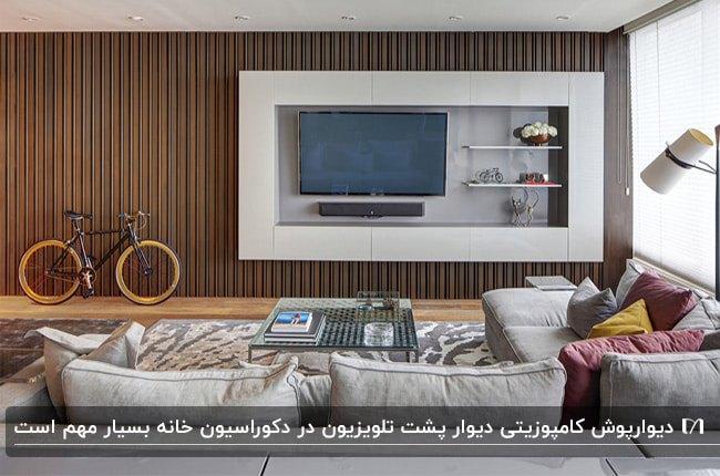 نشیمنی با مبلمان ال شکل طوسی و دیوارپوش کامپوزیتی قهوه ای برای دیوار پشت تلویزیون و یک دوچرخه