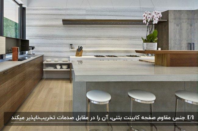 آشپزخانه ای با کابینت های چوبی قهوه ای و جزیره و صفحه کابینت بتونی