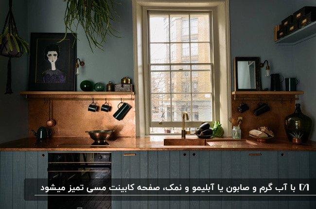 آشپزخانه ای با کابینت ها و دیوار فیلی رنگ و صفحه کابینت مسی