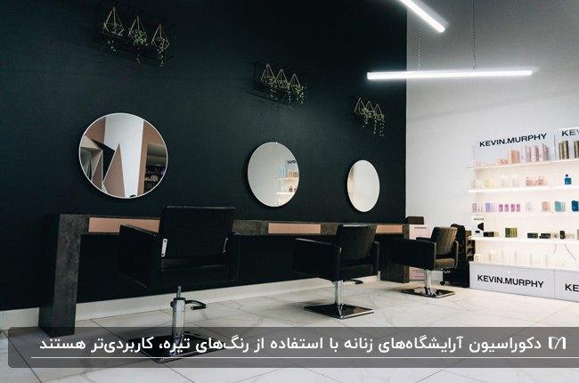 دکوراسیون آرایشگاهی با تم رنگی تیره برای دیوار، میز و صندلی و فریم آینه های گرد