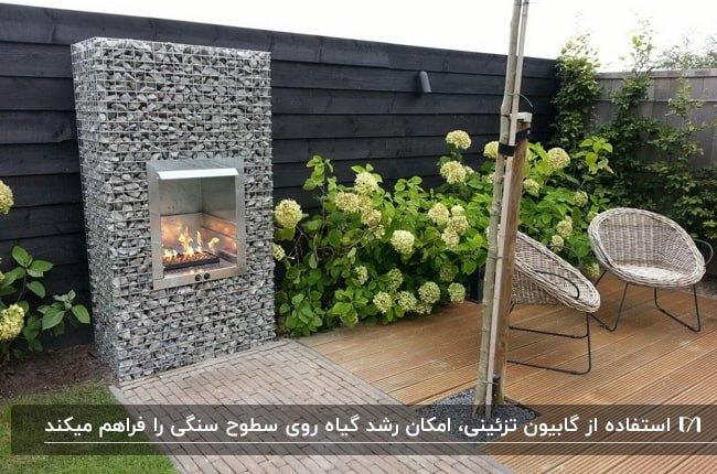 حیاط خانه با دیوار زغالی، دو صندلی حصیری، گل ها و شومینه گابیون
