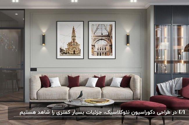 نشیمنی به سبک نئوکلاسیک با مبلمان کرم و زرشکی، دو تابلو و دو چراغ دیوارکوب روی دیوار