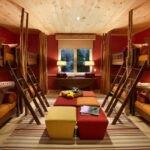 طراحی اتاق خوابگاه با دیوارهای زرشکی، تخت های دو طبقه چوبی، روتختی و پاف های قرمز و زرد