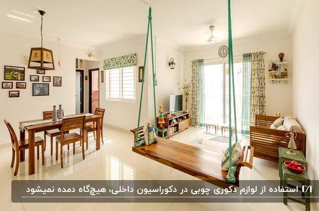 نشیمنی با پرده های طرحدار سفید و سبز و وسایل چوبی تزئینی مثل میزو صندلی های غذاخوری و تاب