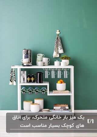 یک میز متحرک سفید رنگ برای کافی بار خانگی مقابل دیوار سبز رنگ