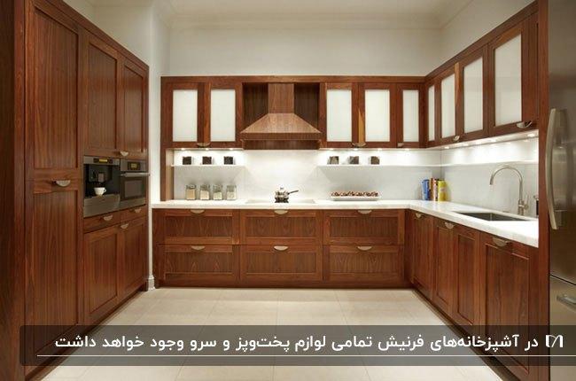 آشزخانه فرنیش بزرگی با کابینت های قهوه ای تیره با درب های شیشه ای نیمه شفاف